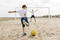 Man and boy playing soccer on the beach - JRFF03423
