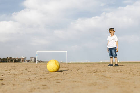 Boy ready to make a shot with a ball on the beach - JRFF03426