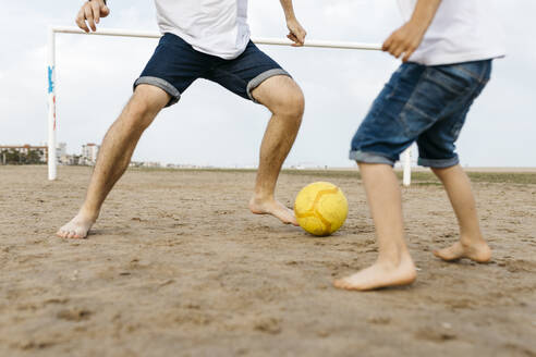 Legs of boy and man playing soccer on the beach - JRFF03429