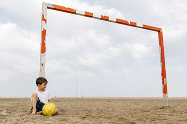Boy sitting on the beach and leaning against soccer goal - JRFF03432