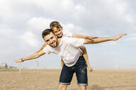 Man carrying boy piggyback on the beach - JRFF03435
