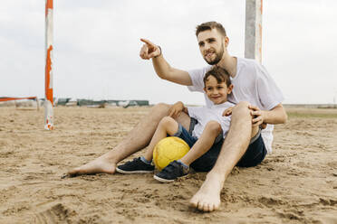 Man and boy resting after soccer game on the beach - JRFF03438