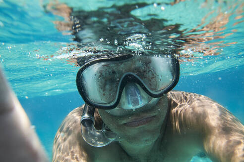 Portrait of man with diving goggles and snorkel taking selfie under water - IGGF01259