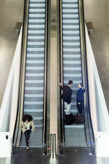 Young business people on an escalator - JSRF00376