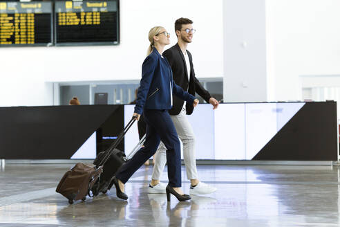 Two young business partners walking at the airport - JSRF00382