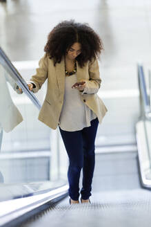Portrait of beautiful young business woman using her mobile phone on escalator. - JSRF00400