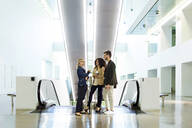Young business people talking at an escalator - JSRF00415