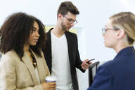 Young business people with takeaway coffee and smartphone - JSRF00418
