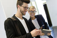 Two smiling young business partners using a smartphone - JSRF00427
