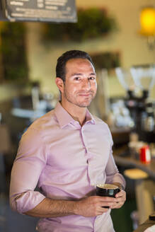 Hispanic businessman drinking coffee in coffee shop - BLEF08239