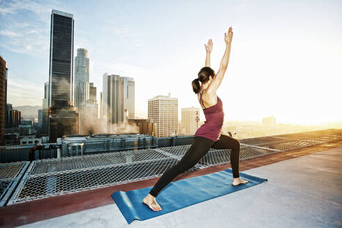 Mixed race woman practicing yoga on urban rooftop - BLEF08281