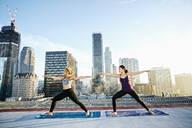 Women practicing yoga on urban rooftop - BLEF08284