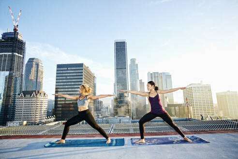 Women practicing yoga on urban rooftop - BLEF08284