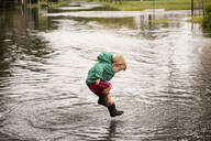 Caucasian boy jumping in puddle - BLEF08296