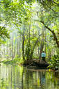 Man standing in boat on tranquil forest river - BLEF08422