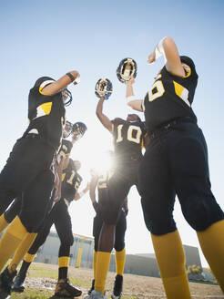 Football players celebrating on football field - BLEF08425