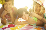 Children in bikinis laying on towel - BLEF08440