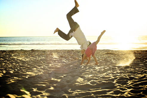 Father and daughter doing cartwheels on beach - BLEF08446
