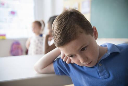 Sad student leaning on desk - BLEF08497