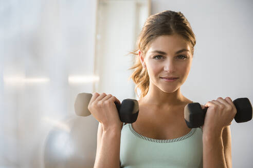 Mixed race woman lifting weights in gym - BLEF08524