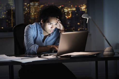 Mixed race businessman working late in office - BLEF08527