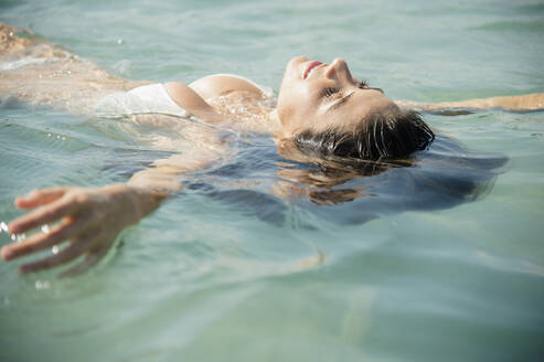 Caucasian woman floating in ocean - BLEF08606