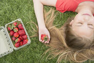 Caucasian girl holding strawberries on grassy lawn - BLEF08627