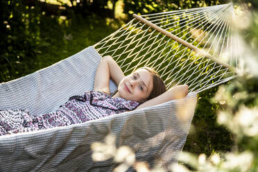 Germany, Bavaria, Landshut, Girl relaxing in hammock in garden - SARF04324