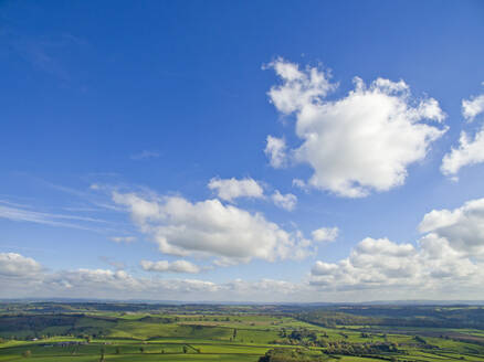 Scenic aerial view of green rolling landscape under sunny blue sky with clouds - JUIF01951