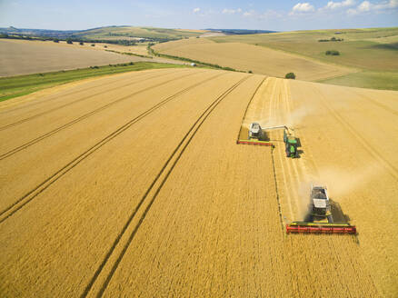 Aerial view of combine harvesters and tractor in sunny golden barley field - JUIF01982