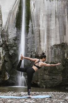 Woman practising yoga at waterfall - LJF00373