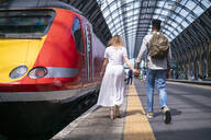 Back view of young couple walking hand in hand on platform, London, UK - FBAF00863