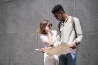 Young couple with city map, London, UK - FBAF00866