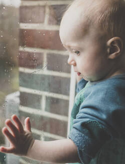 A baby girl looking outside through a window covered with raindrops, Hamburg, DE - IHF00167