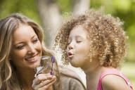 Mother and daughter blowing bubbles - BLEF08790