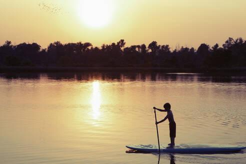 Caucasian boy on paddleboard on lake - BLEF08796