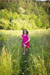 Portrait of little girl smiling while running toward camera across countryside meadow - LVF08133