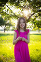 Portrait of little girl wearing vibrant pink dress smiling at camera with blade of grass in hands - LVF08139
