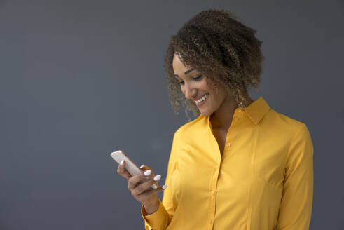 Portrait of smiling young woman wearing yellow shirt looking at cell phone - MOEF02321