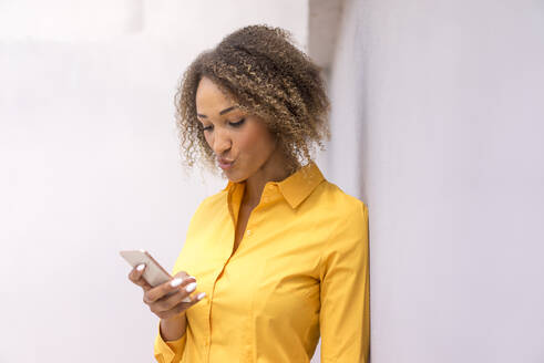 Portrait of young woman wearing yellow shirt looking at cell phone pouting mouth - MOEF02333