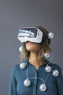 Smiling young woman with chain of lights using Virtual Reality Glasses - MOEF02378