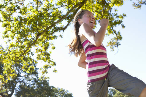 Low angle view of girl running in forest - JUIF02140