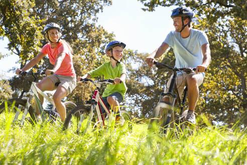Family riding mountain bikes in rural field - JUIF02173