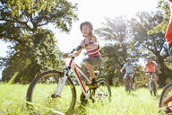 Family riding mountain bikes in rural field - JUIF02176