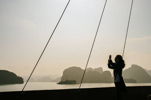 Caucasian woman photographing rock formations in Ha Long Bay, Vietnam - BLEF09023