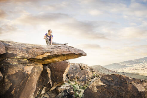Caucasian woman stretching on rock formation - BLEF09113