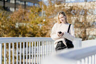 Portrait of smiling young woman standing on footbridge in autumn looking at cell phone - GIOF06588