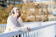 Portrait of happy young woman leaning on railing of footbridge listening music with headphones - GIOF06591