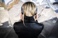 Back view of blond  young woman listening music with wireless headphones - GIOF06606