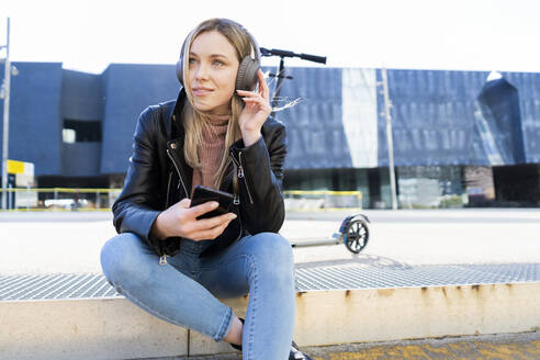 Portrait of young woman listening music with smartphone and headphones, Barcelona, Spain - GIOF06612